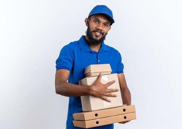 Uśmiechnięty młody afro-amerykański mężczyzna dostawy trzymający karton i opakowanie żywności na pudełkach po pizzy na białym tle na białej ścianie z miejscem na kopię