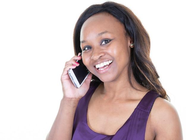 Uśmiechnięty młody afro kobieta amerykanin opowiada na telefonie komórkowym