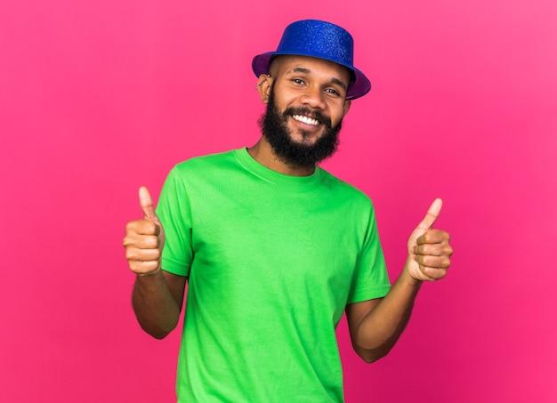 Uśmiechnięty młody afroamerykański facet w imprezowym kapeluszu pokazujący kciuki do góry odizolowany na różowej ścianie