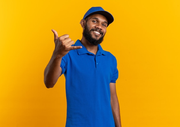 Uśmiechnięty młody afroamerykański mężczyzna dostawy gestykuluje powiesić luźny znak na pomarańczowym tle z kopią miejsca