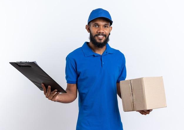 Uśmiechnięty młody afroamerykański mężczyzna dostawy trzymający karton i schowek na białym tle na białej ścianie z miejscem na kopię