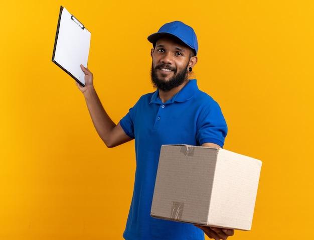 Uśmiechnięty młody afroamerykański mężczyzna dostawy trzymający karton i schowek na białym tle na pomarańczowym tle z miejscem na kopię