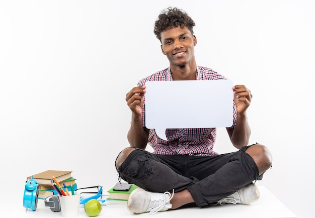 Uśmiechnięty młody afroamerykański uczeń siedzący na biurku z szkolnymi narzędziami trzymający dymek