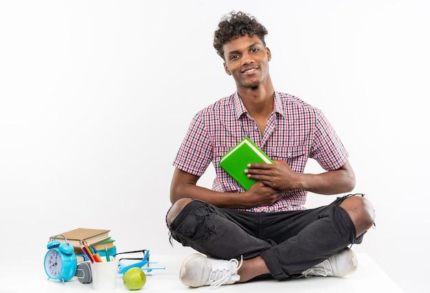 Uśmiechnięty młody afroamerykański uczeń siedzący na biurku z szkolnymi narzędziami trzymającymi książkę