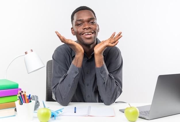 Uśmiechnięty młody afroamerykański uczeń siedzący przy biurku ze szkolnymi narzędziami trzymającymi ręce otwarte