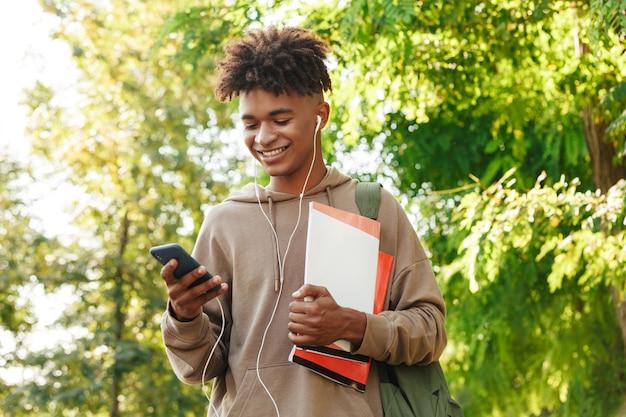 Uśmiechnięty młody afrykański facet z plecakiem