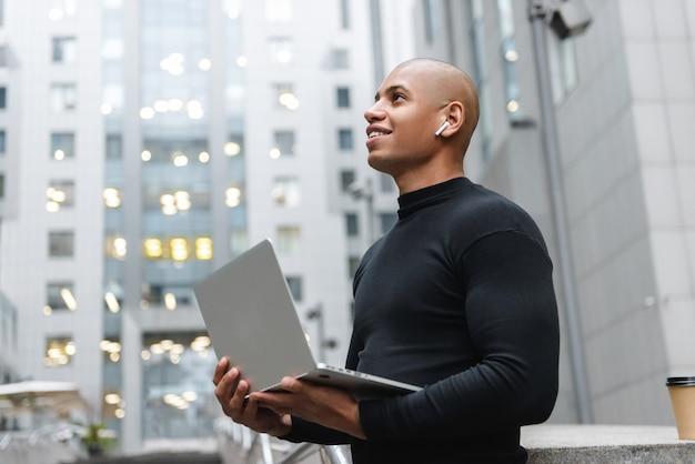 Uśmiechnięty młody afrykański mężczyzna stojący na ulicy miasta, pracujący na laptopie