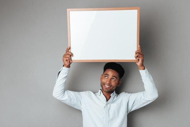 Uśmiechnięty młody afrykański mężczyzna trzyma puste miejsce deskę nad jego głową