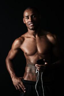 Uśmiechnięty młody afrykański sporta mężczyzna mienia telefon komórkowy