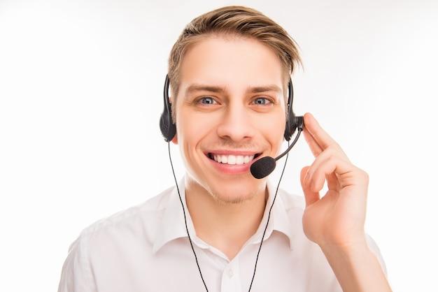 Uśmiechnięty młody agent call center dotykając słuchawek
