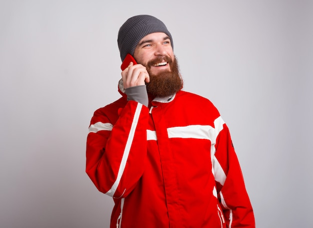 Uśmiechnięty młody alpinista mężczyzna opowiada na smartphone