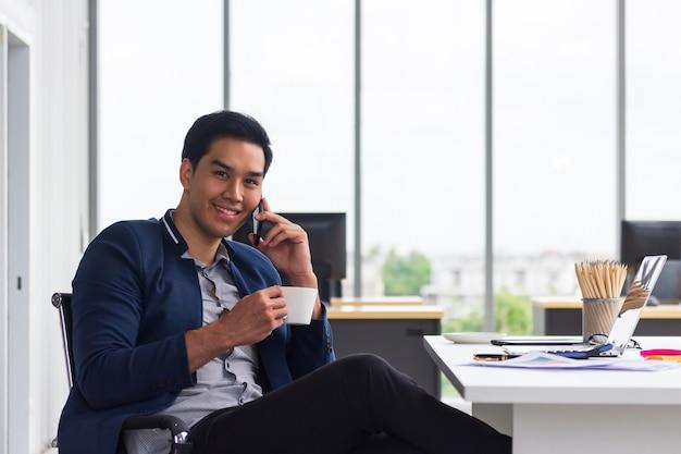 Uśmiechnięty młody azjatykci biznesmen opowiada na jego telefonie komórkowym i pije kawę w biurze z laptopem.