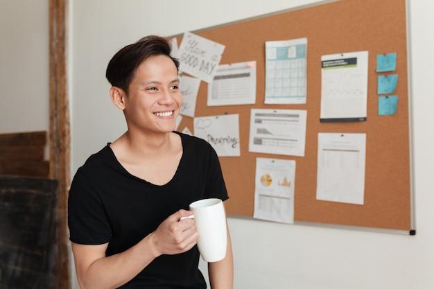 Uśmiechnięty młody azjatykci mężczyzna stoi indoors pije herbaty.