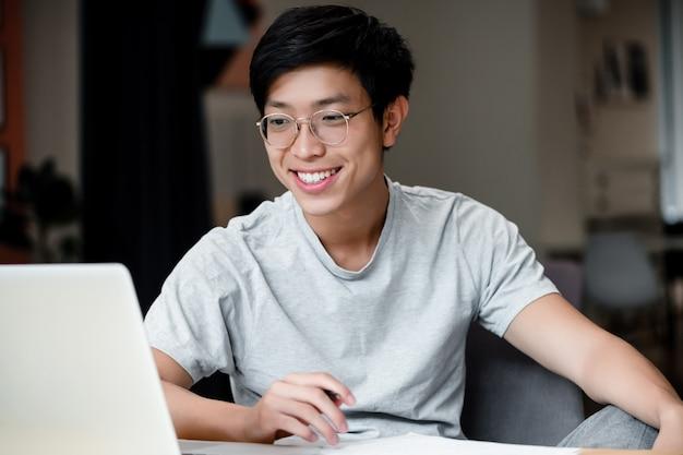 Uśmiechnięty młody azjatykci mężczyzna w biurze z laptopem