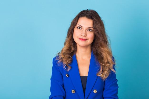 Uśmiechnięty młody biznes kobieta portret na niebieskim tle.