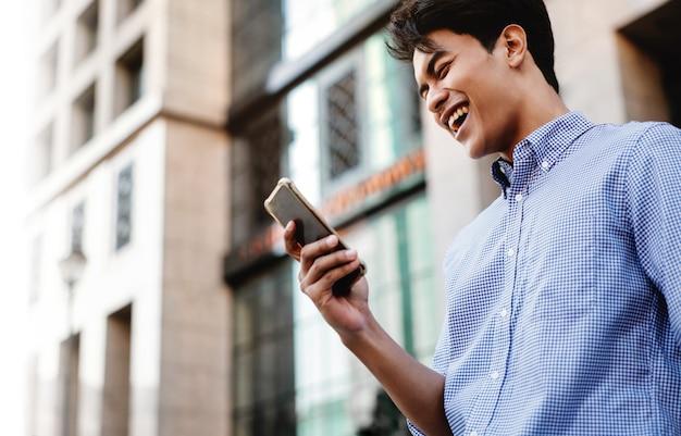 Uśmiechnięty młody biznesmen azjatyckich za pomocą telefonu komórkowego w mieście