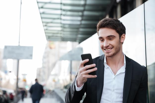Uśmiechnięty młody biznesmen chodzi blisko centrum biznesu.