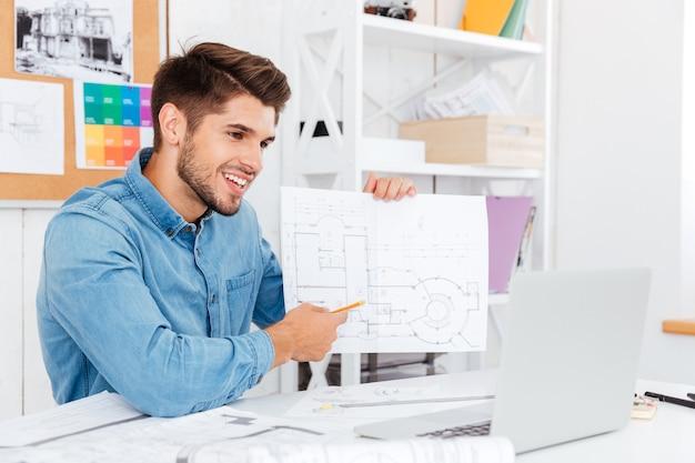 Uśmiechnięty młody biznesmen dorywczo pokazujący dokumenty na aparacie siedząc w biurze