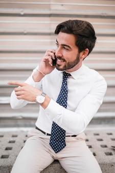 Uśmiechnięty młody biznesmen gestykuluje podczas gdy opowiadający na smartphone