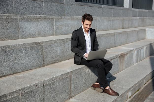 Uśmiechnięty młody biznesmen siedzi outdoors.