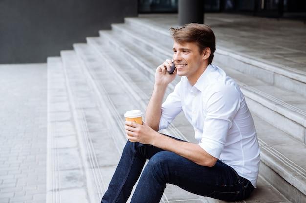 Uśmiechnięty młody biznesmen stojący w pobliżu centrum biznesowego i picia kawy