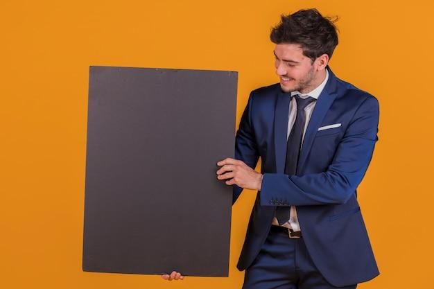 Uśmiechnięty młody biznesmen trzyma pustego czarnego plakat przeciw pomarańczowemu tłu