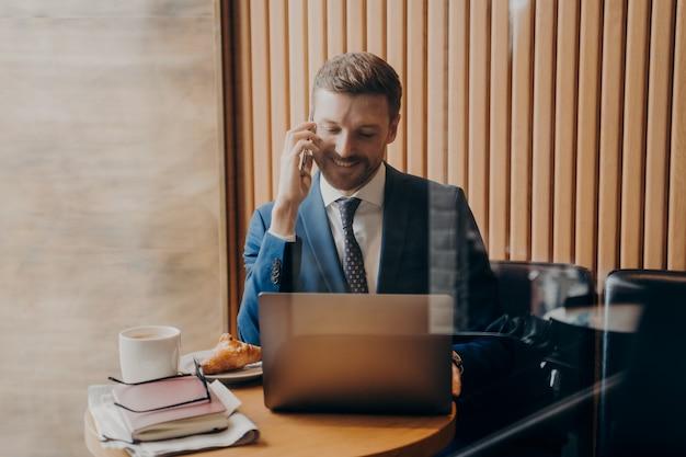 Uśmiechnięty młody biznesmen w niebieskim garniturze formalnym z krawatem rozmawiając z p na partnerze telefonu podczas pracy z dala od biura w kawiarni na swoim laptopie, po kawie i rogaliku. koncepcja freelancera