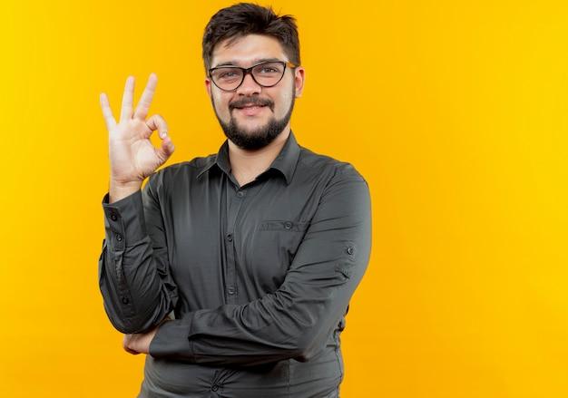 Uśmiechnięty młody biznesmen w okularach pokazujących okey gest na żółtym tle