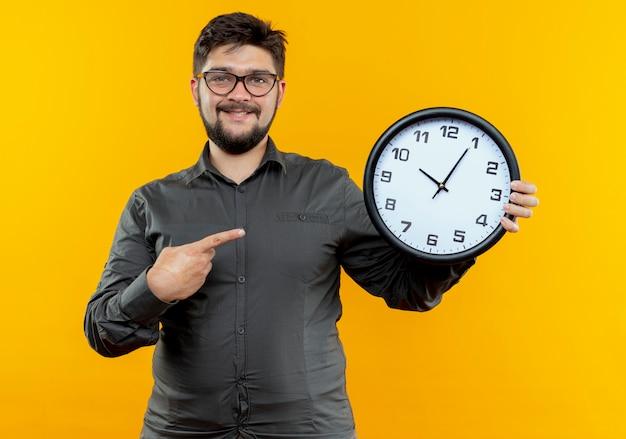 Uśmiechnięty młody biznesmen w okularach trzyma i wskazuje na zegar ścienny na żółtym tle