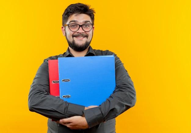 Uśmiechnięty młody biznesmen w okularach trzymając foldery odizolowane na żółto