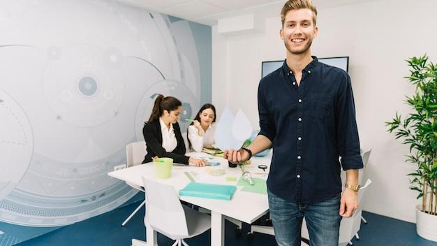 Uśmiechnięty młody biznesmen z wody kropli ikony pozycją w biurze