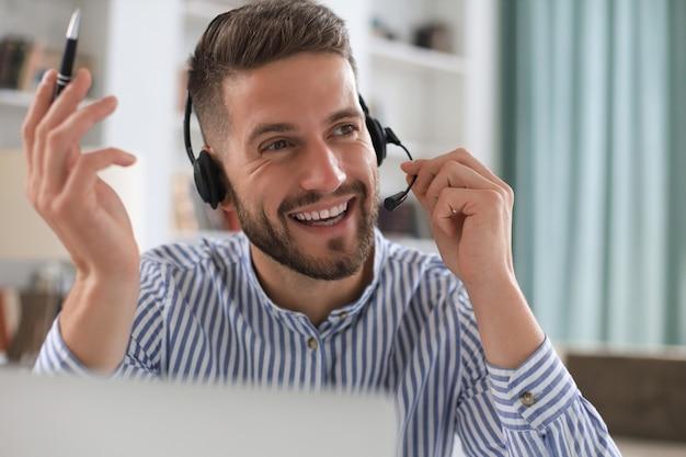 Uśmiechnięty młody biznesowy mężczyzna o wideorozmowę w biurze.