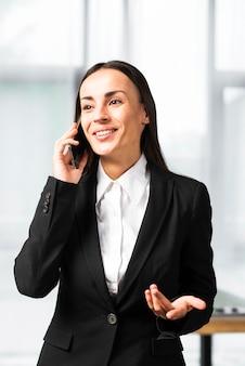 Uśmiechnięty młody bizneswoman bierze na telefon komórkowy wzrusza ramionami