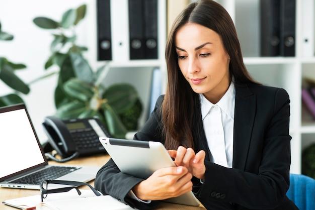Uśmiechnięty młody bizneswoman używa cyfrową pastylkę w biurze