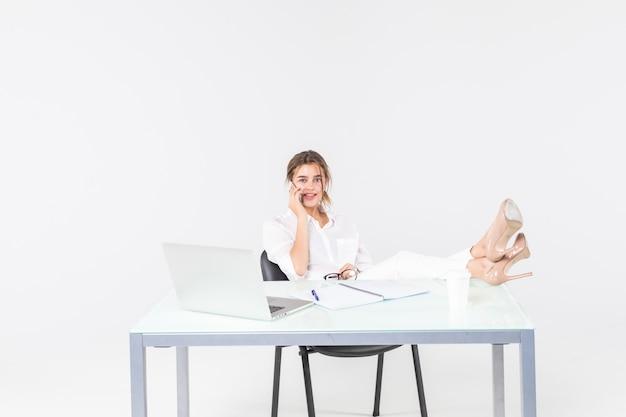 Uśmiechnięty młody bizneswoman używa laptop i pisać z nogami na biurku odizolowywającym nad białym tłem
