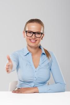 Uśmiechnięty młody bizneswoman ze znakiem powitalnym ręki