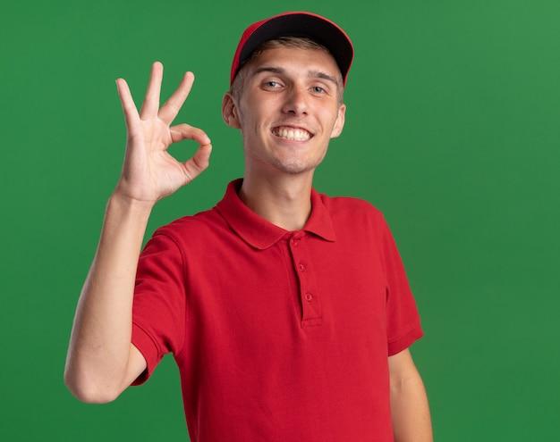 Uśmiechnięty młody blond chłopiec dostawczy gestykuluje znak ręką na zielonej ścianie z kopią miejsca