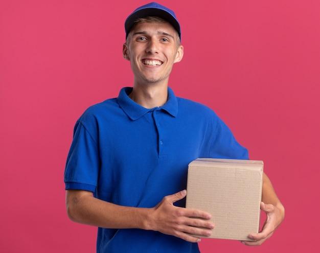 Uśmiechnięty młody blond chłopiec dostawczy trzyma karton na różowej ścianie z miejscem na kopię