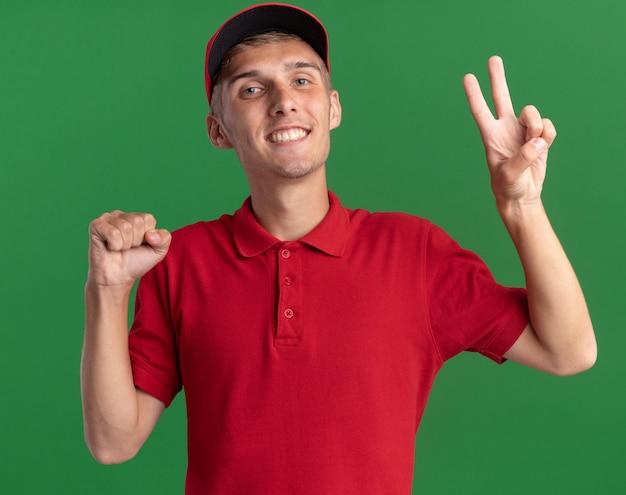 Uśmiechnięty młody blond chłopiec dostawczy trzyma pięść i gestykuluje znak zwycięstwa na zielonej ścianie z miejscem na kopię