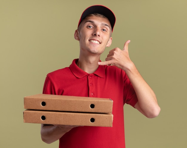 Uśmiechnięty młody blond chłopiec dostawczy trzyma pudełka po pizzy i gesty nazywają mnie znakiem na oliwkowej zieleni