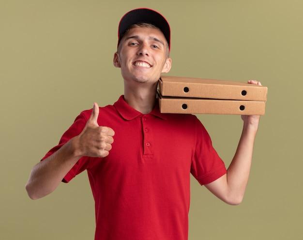 Uśmiechnięty młody blond chłopiec dostawy kciuki do góry i trzyma pudełka po pizzy na ramieniu na oliwkowej zieleni