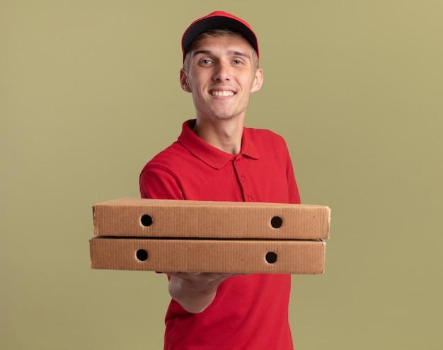 Uśmiechnięty młody blond chłopiec dostawy trzymający pudełka po pizzy patrząc na kamerę