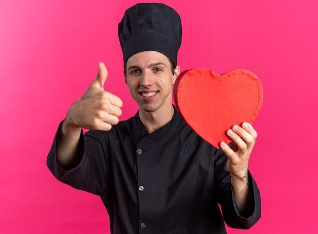 Uśmiechnięty młody blond kucharz w mundurze szefa kuchni i czapce, patrząc na kamerę pokazującą kształt serca i kciuk w górę na różowej ścianie