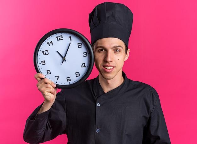 Uśmiechnięty młody blond kucharz w mundurze szefa kuchni i czapce, trzymający zegar dotykający nim twarzy