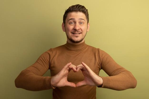 Uśmiechnięty młody blond przystojny mężczyzna patrzący na znak serca na oliwkowozielonej ścianie