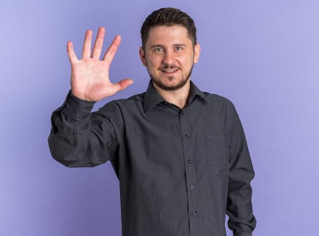 Uśmiechnięty młody blond przystojny mężczyzna pokazuje numer pięć ręką patrząc na kamerę