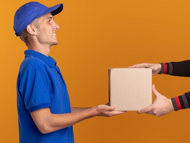 Uśmiechnięty młody blondyn-dostawca stoi bokiem i daje komuś karton