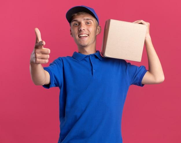 Uśmiechnięty młody blondyn-dostawca trzyma karton na ramieniu i wskazuje na kamerę odizolowaną na różowej ścianie z miejscem na kopię