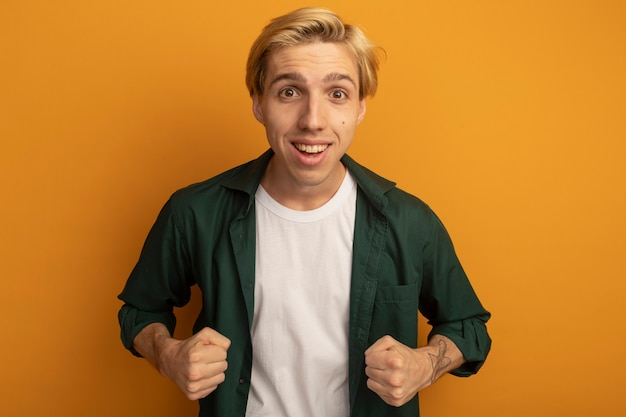 Uśmiechnięty młody blondyn na sobie zieloną koszulkę pokazuje tak gest