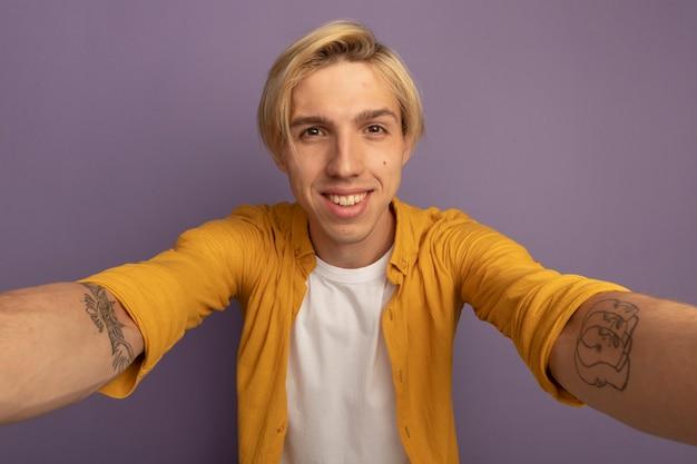 Uśmiechnięty młody blondyn na sobie żółtą koszulkę trzymając aparat na białym tle na fioletowo